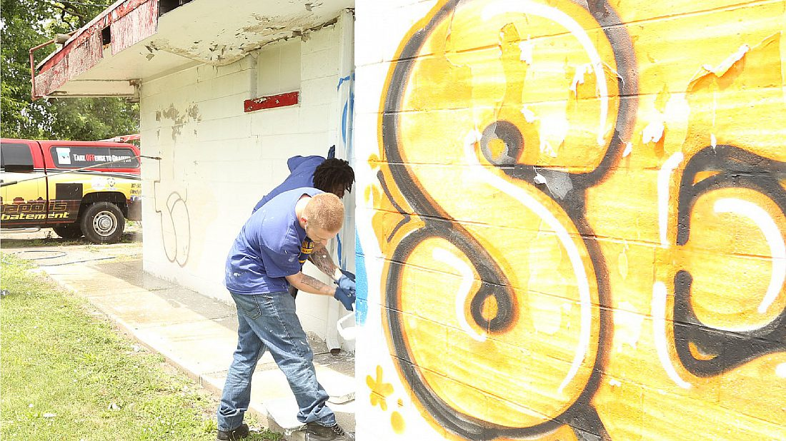 Two young volunteers helping to clean up graffiti.